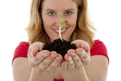 New Life. Woman is holding Pile of black garden soil with young plant for new life over white background stock image