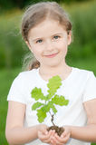 New life. Little girl and young oak tree Stock Image