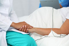 New life of abortion concept. Friendly female medicine doctor hands holding pregnant woman's hand lying in bed for encouragement, empathy, cheering and support stock images