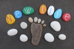 New Life concept with colored stones composition over black volcanic sand. Original New Life text for a better future with colored stones design and a wooden stock photo