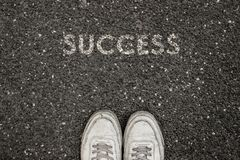 New Life Concept, Motivational Slogan with Word SUCCESS on the ground of asphalt royalty free stock image