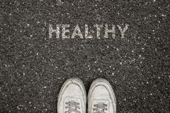 New life concept, Sport shoes and the word HEALTHY ! written on asphalt ground, Motivational slogan stock images