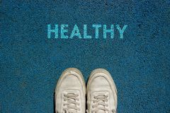 New life concept, Sport shoes and the word HEALTHY ! written on blue Walkway ground, Motivational slogan royalty free stock image