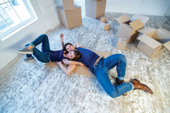 New life. Couple in love moving and keep a box in his hands and Stock Images