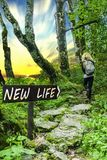 New Life Arrowed Wooden Sign in Forest with Person and Sunset. New life motivational phrase on wooden sing with person walking on forest stone road into the stock images