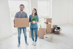 New life, new start, new home for a young family. What a joy! Ha. Ppy cheerful lovers are unpacking in a new apartment, standing in a casual wear royalty free stock photography