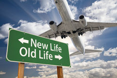 New Life, Old Life Green Road Sign and Airplane Above royalty free stock photo