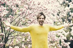 New life and optimism. Guy in yellow sweater with open hands on floral background. Flourishing, nature, growth. Spring season concept. Man smile in park with royalty free stock images