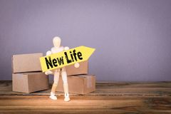 New Life. Wooden man with yellow an arrow and cardboard boxes. New Life concept. Wooden man with yellow an arrow and cardboard boxes royalty free stock photography