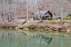 New Log Cabin on Bank of River in Winter Royalty Free Stock Photo