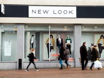 New Look shopfront with people,blurred, walking past. The front of a New Look store in Bournemouth with dressed mannequins in the window with people,blurred Royalty Free Stock Photography