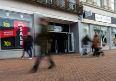 New Look store front with sale sign. The frontage of a New Look store showing sale signs with blurred pedestrians walking past Stock Photo