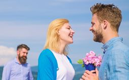 New love. Ex partner watching girl starts happy love relations. Ex husband jealous on background. Couple in love dating. Outdoor sunny day, sky background royalty free stock images