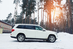 New luxury auto Mercedes parked in forest at winter evening. Stock Photography