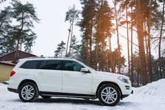 New luxury crossover Mercedes parked in forest at winter evening. Stock Images