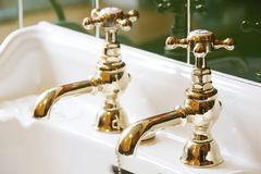Free New Luxury Hotel Vintage Brass Gold Plated Pillar Taps In Ensuite Bathroom At Wash Basin Royalty Free Stock Photos - 156835428