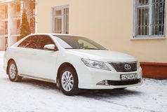 New luxury Toyota Camry parked near the house at winter evening. Stock Photo