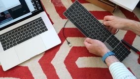 New magic keyboard with numeric keypad space gray unboxing. London, United Kingdom - Apr 15, 2018: Man unboxing installing charging pairing Bluetooth to Apple stock video footage