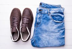 New male shoes and jeans on wooden table. Top view Stock Photography