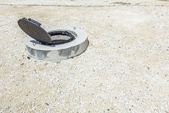 New manhole in compacted gravel. View on assembled new manhole with opened metal cover at construction site Stock Image
