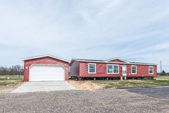 Early Stages of Manufactured Home Community. New manufactured home with red vinyl siding and windows with white lineals still needs some work stock image