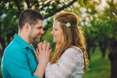 New married couple holding their hands in cherry wood at sunset Stock Photos