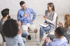 Happy people clapping at support group meeting stock images