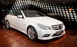 New Mercedes E class cabriolet. In white color in the showroom New Mercedes E class in the showroom on Champs-Élysées in Paris. Car located among colorful Stock Image