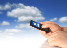 New message. Mobile phone in hand over blue sky background Stock Photo