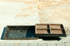 New metal cover over concrete manhole at road construction site close up. royalty free stock photos