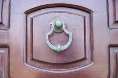 New metal doorknocker on wooden closed brown door. Closeup Stock Images