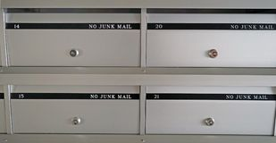 New metal mailboxes in an apartment building with flat numbers stock photos