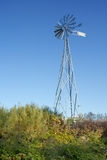 New metal windmill in a garden. Royalty Free Stock Images