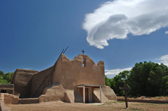 New Mexico Adobe Church. An old adobe church bathed in sun beneath strange cloud formation on a native American pueblo royalty free stock photos