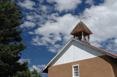 New Mexico Adobe Church. An old adobe church with bell tower beneath the puffy white clouds of the New Mexico countryside royalty free stock photos