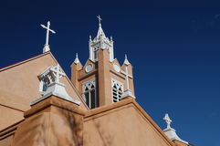 New Mexico Adobe Church. The roofline of an adobe style church in Albuquwerque is outlined against the deep blue winter sky in New Mexico stock image