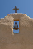 New Mexico Church Bell. Church Bell hangs from an opening in a New Mexico adobe church wall beneath a crucifix stock images