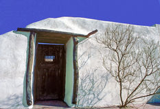 New Mexico Door and Wall. New Mexico style door and wall with barren tree beside door making for an interesting design Stock Image