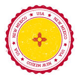 New Mexico flag badge. Grunge rubber stamp with New Mexico flag. Vintage travel stamp with circular text, stars and USA state flag inside it. Vector Royalty Free Stock Images