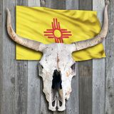 New Mexico flag and Cow Skull. New Mexico flag and old cow skull on wooden background Royalty Free Stock Photos