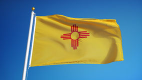 New Mexico flag in slow motion seamlessly looped with alpha. New Mexico flag waving in slow motion against clean blue sky, seamlessly looped, close up, isolated stock video footage