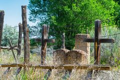 New Mexico Graveyard with Crosses and Headstones. Old New Mexico Graveyard with Wood Crosses and Headstones, an old Ladder and Barbed Wire Fence, Tall Grass and royalty free stock photos