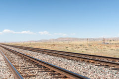 New Mexico high plains landscapes alongside Route 66. New Mexico high plains landscapes and railway alongside Route 66 with distant mesa land forms royalty free stock photography