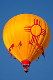New Mexico Hot Air Balloon. Yellow hot air Balloon with Zia Sun symbol, a feature of the New Mexico state flag. Blue sky stock images