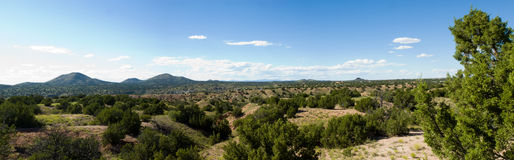 New Mexico plains. Panorama of the plains of Northern New Mexico, with bushes and vegetation stretching towards distant mountains Stock Photo