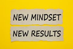 New mindset new results concept. NEW MINDSET, NEW RESULTS written on old torn paper on yellow background. Business Concept. Top view Stock Photo