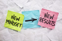 New mindset and results. New mindset and new results concept - colorful sticky notes on a background of crumpled white notes stock images