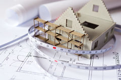 New model house with scaffolding on architecture blueprint plan royalty free stock photography
