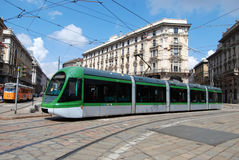 New model tram (tramcar, trolley) in Milan. Typical tram (New model) in Milan square. A tram, tramcar, trolley, trolley car, or streetcar is a railborne vehicle Stock Photos
