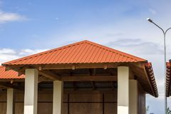New modern alcove on kindergarten playground with bright orange tiling roof on blue sky background. stock image